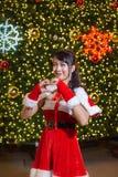 Счастливая усмехаясь девушка Санта мила в красном костюме и рука любит сердце с предпосылкой рождественской елки стоковое изображение rf
