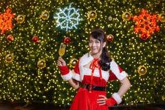 Счастливая усмехаясь девушка Санта мила в красном костюме и руке держа шампанское с предпосылкой рождественской елки стоковое фото