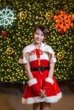 Счастливая усмехаясь девушка Санта мила в красном костюме с торжеством предпосылки рождественской елки в рождестве стоковое изображение