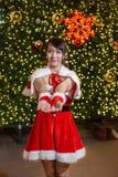 Счастливая усмехаясь девушка Санта мила в красном костюме с торжеством предпосылки рождественской елки в рождестве стоковая фотография rf