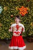 Счастливая усмехаясь девушка Санта мила в красном костюме с торжеством предпосылки рождественской елки в рождестве стоковое фото