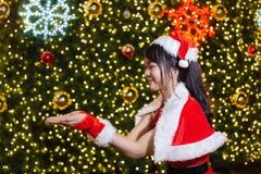 Счастливая усмехаясь девушка Санта мила в красном костюме с торжеством предпосылки рождественской елки в рождестве стоковая фотография