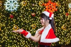 Счастливая усмехаясь девушка Санта мила в красном костюме с торжеством предпосылки рождественской елки в рождестве стоковые изображения