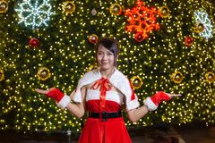 Счастливая усмехаясь девушка Санта мила в красном костюме с торжеством предпосылки рождественской елки в рождестве стоковое фото rf