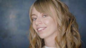 Счастливая усмехаясь девушка с красивым белокурым вьющиеся волосы представляя в студии красоты видеоматериал