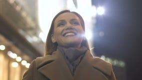 Счастливая усмехаясь женщина в ее 30s двигая на освещенную улицу города, выравнивая прогулку видеоматериал