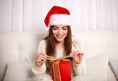 Счастливая усмехаясь женщина в красной шляпе рождества с подарком на кровати Стоковая Фотография RF