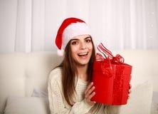Счастливая усмехаясь женщина в красной шляпе рождества с подарком на кровати Стоковое фото RF