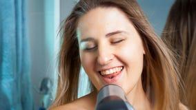 Счастливая усмехаясь женщина поя с феном для волос на ванной комнате стоковые фото