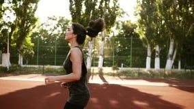 Счастливая, усмехаясь кавказская девушка при хвост бежать outdoors на день лета солнечный Большой стадион с коричневым заволакива видеоматериал