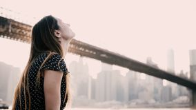 Счастливая усмехаясь кавказская молодая женщина сидя на загородке обваловки реки, наслаждаясь панорамой 4K Бруклинского моста Нью акции видеоматериалы