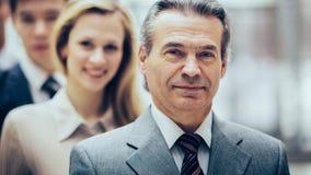 Счастливая усмехаясь команда дела стоя в строке на офисе стоковые фото