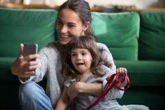 Счастливая усмехаясь мать принимая selfie с дочерью стоковая фотография