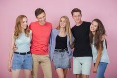 Счастливая усмехаясь молодая группа в составе друзья стоя совместно говоря и смеясь Лучшие други стоковая фотография