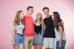 Счастливая усмехаясь молодая группа в составе друзья стоя совместно говоря и смеясь Лучшие други стоковое фото rf