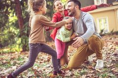 Счастливая усмехаясь семья бежать и играя на задворк Стоковые Изображения RF