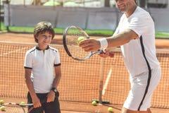 Счастливая усмехаясь семья играя теннис Стоковая Фотография