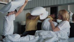 Счастливая усмехаясь семья на кровати при подушка играя на кровати с белыми листами Концепция счастливой семьи сток-видео