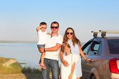 Счастливая усмехаясь семья с 2 детьми автомобилем с backgroun моря стоковое изображение