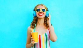 Счастливая усмехаясь чашка удерживания женщины сока слушая музыку в беспроводных наушниках на красочной сини стоковые изображения