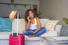 Счастливая черная афро американская женщина с чемоданом говоря на мобильном телефоне сидя на кресле софы выходя на праздники заде стоковое фото rf