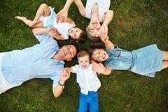 Счастливая шаловливая семья лежа на траве outdoors родители с детьми летом Мама, папа и дети стоковые изображения rf
