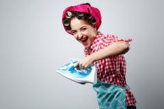 Счастливая шальная девушка с утюгом стоковые фото