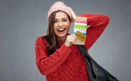 Счастливая эмоциональная женщина нося красный свитер держа билет и шаг стоковое фото