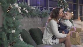 Счастливая excited мать молодой женщины играя с ее младенцем мальчика в рождественской елке украсила праздничную уютную комнату с сток-видео
