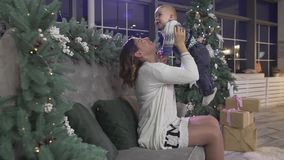 Счастливая excited мать молодой женщины играя с ее ребёнком в рождественской елке украсила праздничную уютную комнату студии сток-видео