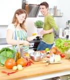 Счастливая sporty пара подготавливает здоровую еду на светлой кухне стоковые изображения