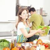 Счастливая sporty пара подготавливает здоровую еду на светлой кухне стоковая фотография