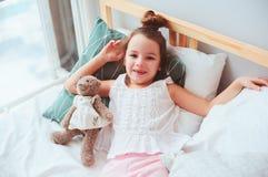 счастливое бодрствование девушки ребенка вверх в раннем утре в ее комнате стоковое изображение
