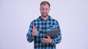 Счастливое бородатое чтение человека хипстера на доске сзажимом для бумаги и давать больших пальцах руки вверх видеоматериал
