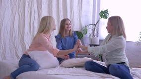 Счастливое время с матерью, веселые мама семьи и дочери обнимают и целуют во время сообщения на кровати