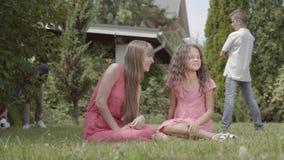 Счастливое время траты семьи в саде совместно Мать и дочь сидя на переднем плане, ребенок чихая видеоматериал
