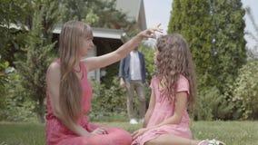 Счастливое время траты семьи в саде совместно Мать и дочь сидя на переднем плане Игра отца видеоматериал