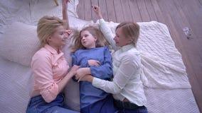Счастливое детство, смеясь мама с девушками детей лежит на кровати и связывает друг с другом