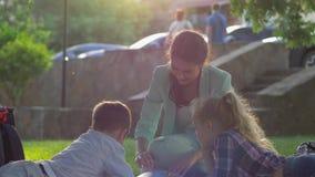 Счастливое детство, усмехаясь мать прочитало книгу для мальчика и девушки сидя на зеленой лужайке в природе в солнечном свете видеоматериал