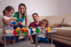 Счастливое единение семьи Родитель играя с детьми дома стоковое фото
