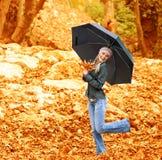Счастливое женское танцы с парасолем Стоковая Фотография RF