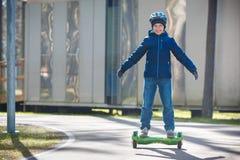 Счастливое катание мальчика на само-балансируя палубе в парке города стоковая фотография