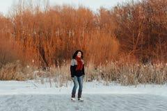 Счастливое катание на коньках женщины на замороженном пруде на заходе солнца Стоковое Изображение RF