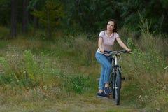 Счастливое красивое катание девушки на велосипеде в лесе Стоковая Фотография