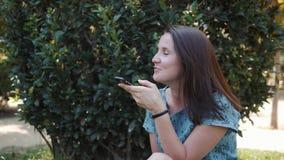Счастливое лето брюнета женщины маленькой девочки сидя outdoors в парке, используя мобильный телефон с аудио ai опознавания голос сток-видео