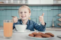 Счастливое ликование маленькой девочки и блюдо иметь стоковое изображение