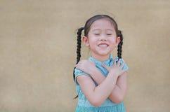 Счастливое маленькое азиатское выражение девушки ребенка пересечь one руку и закрытые глаза Уверенные и жизнерадостные дети стоковое фото rf