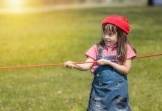Счастливое маленькое gril играя перетягивание каната веревочки в парке стоковая фотография rf