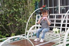 Счастливое милое капризное симпатичное прелестное lolipop игры маленькой девочки и сидит на экипаже имеет потеху внешнюю в парке  Стоковое Изображение