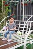 Счастливое милое капризное симпатичное прелестное lolipop игры маленькой девочки и сидит на экипаже имеет потеху внешнюю в парке  Стоковая Фотография